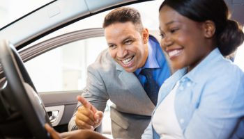 beautiful african american woman buying a car at dealership